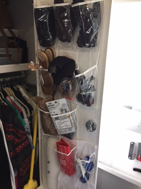 Clear plastic hanging shoe rack on the inside of a small white closet door.